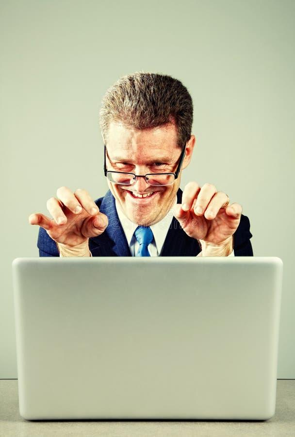 Homme d'affaires fol sur l'ordinateur portable photographie stock
