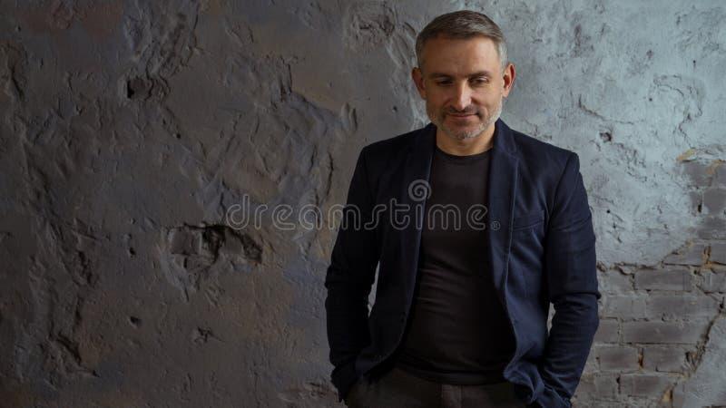 Homme d'affaires frais avec la position grise de cheveux et de barbe sur le fond gris photos libres de droits
