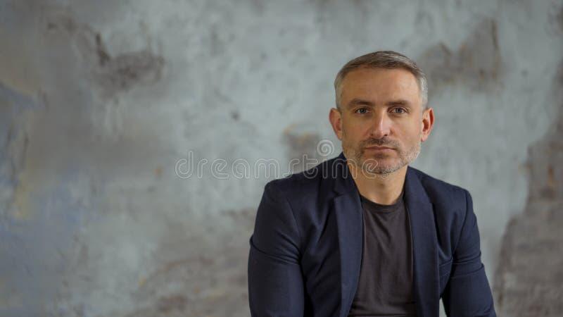 Homme d'affaires frais avec la position grise de cheveux et de barbe sur le fond gris images libres de droits