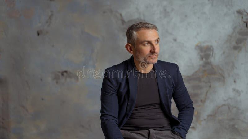 Homme d'affaires frais avec les cheveux gris et barbe se reposant sur le fond gris photo libre de droits
