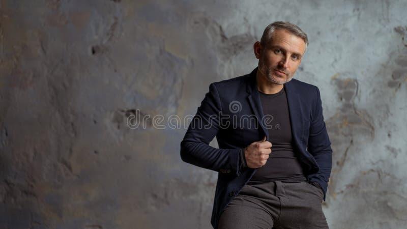 Homme d'affaires frais avec les cheveux gris et barbe sur le fond gris image libre de droits
