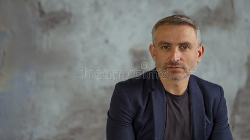 Homme d'affaires frais avec les cheveux gris et barbe sur le fond gris image stock