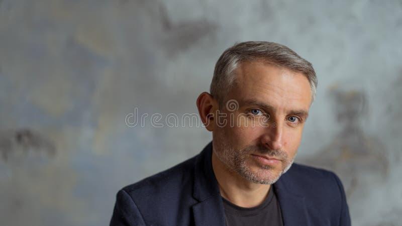 Homme d'affaires frais avec les cheveux gris et barbe sur le fond gris photo libre de droits