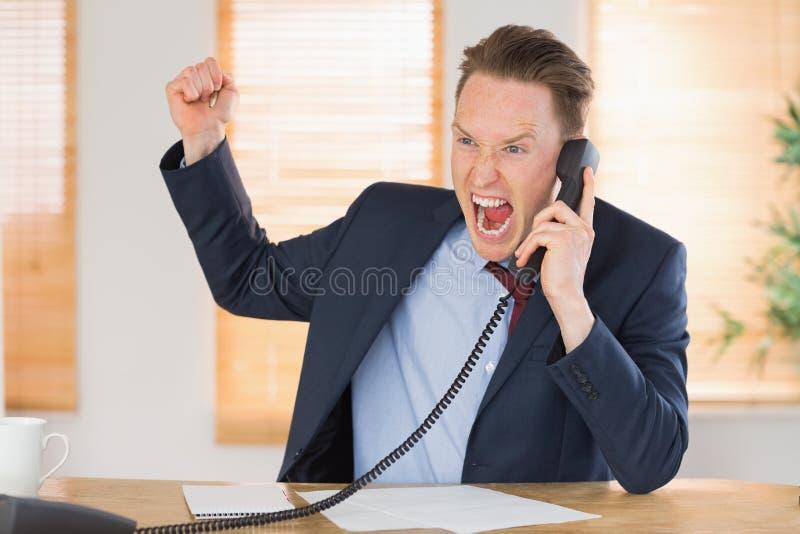 Homme d'affaires furieux outragé au téléphone photos libres de droits