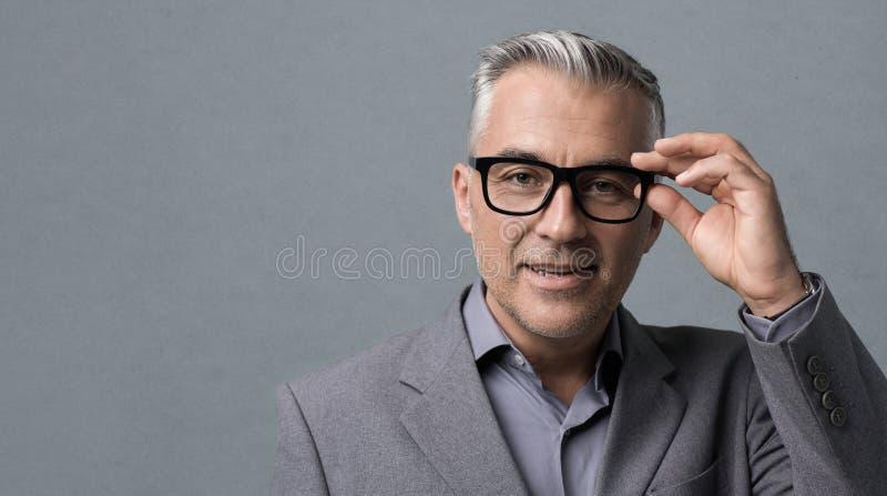 Homme d'affaires futé avec la pose en verre photo stock
