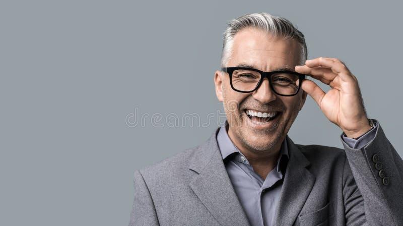Homme d'affaires futé avec la pose en verre photographie stock libre de droits
