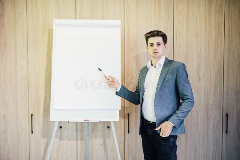 Homme d'affaires futé présent quelque chose sur le tableau de conférence dans le bureau moderne photo libre de droits