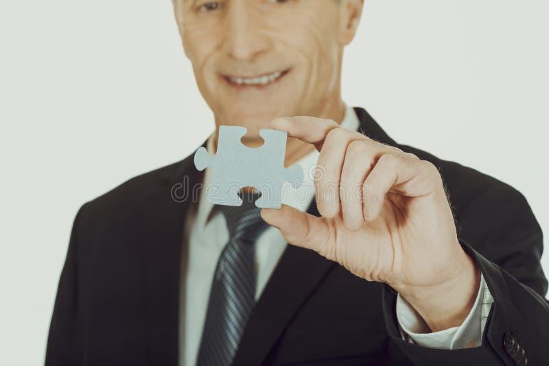 Homme d'affaires futé tenant un puzzle photos stock