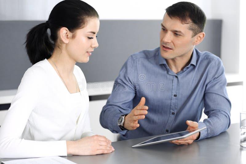 Homme d'affaires gai et femme de sourire travaillant avec la tablette dans le bureau moderne Headshot sur se réunir ou lieu de tr photos stock