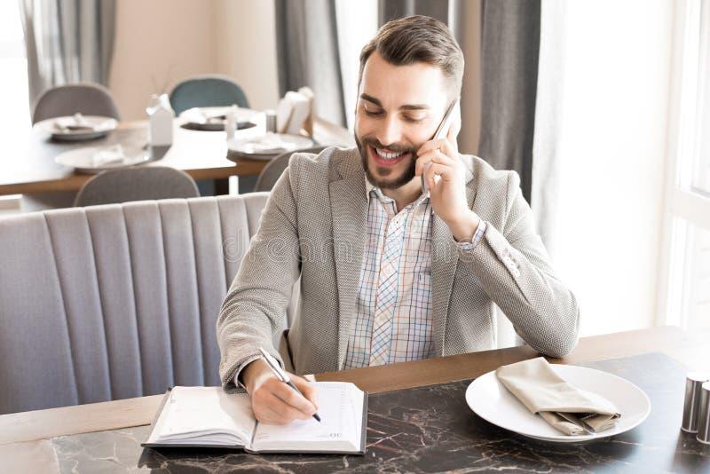 Homme d'affaires gai Working en café photographie stock libre de droits