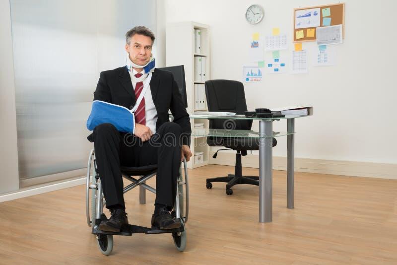 Homme d'affaires handicapé s'asseyant sur le fauteuil roulant photographie stock libre de droits
