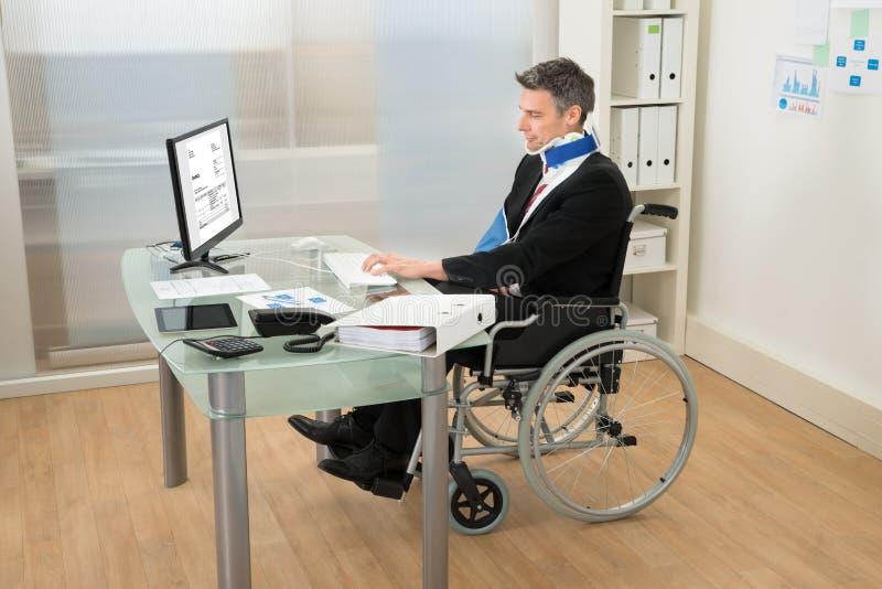 Homme d'affaires handicapé utilisant l'ordinateur photos stock
