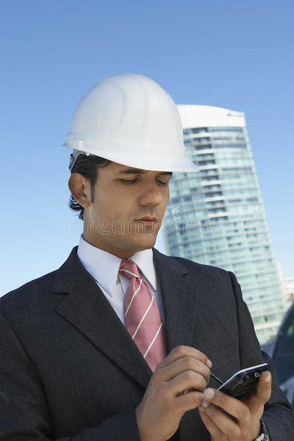 Homme d'affaires In Hardhat Using PDA photographie stock