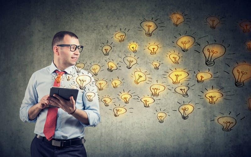 Homme d'affaires heureux à l'aide de la tablette ayant des idées brillantes étant créatives photos libres de droits