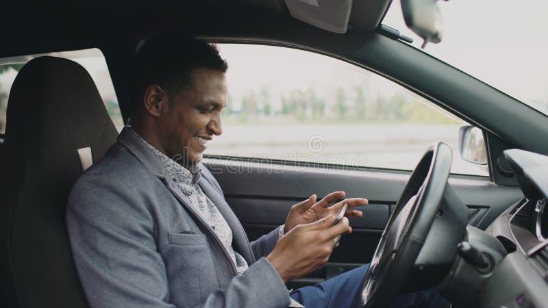 Homme d'affaires heureux d'afro-américain surfant le media social sur sa tablette se reposant à l'intérieur de sa voiture image stock