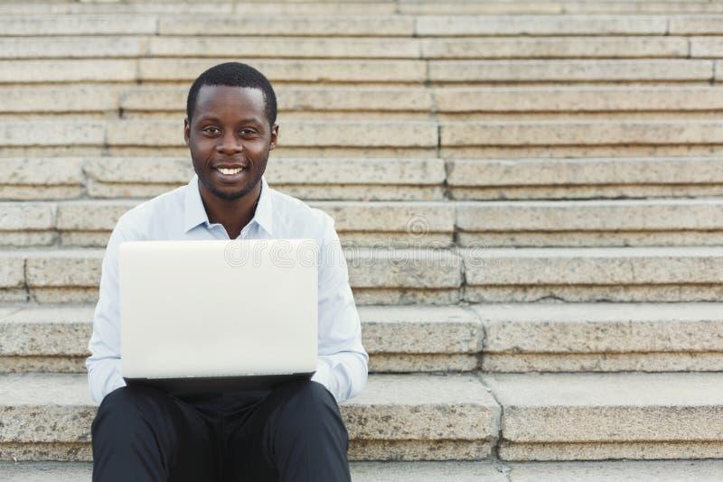 Homme d'affaires heureux d'afro-américain travaillant avec l'ordinateur portable dehors images stock