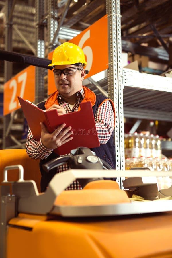Homme d'affaires heureux avec le presse-papiers à l'entrepôt images stock