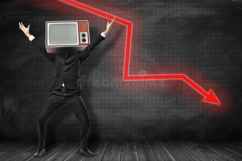 Homme d'affaires heureux avec le rétro poste TV au lieu de la tête et de la flèche rouge allant vers le bas sur le fond noir photos libres de droits