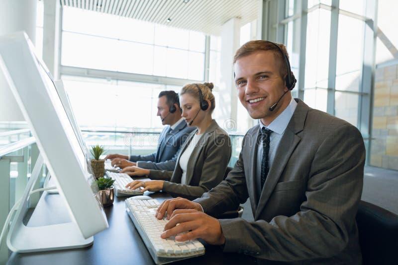 Homme d'affaires heureux avec ses collègues travaillant sur l'ordinateur au bureau dans le bureau photos stock