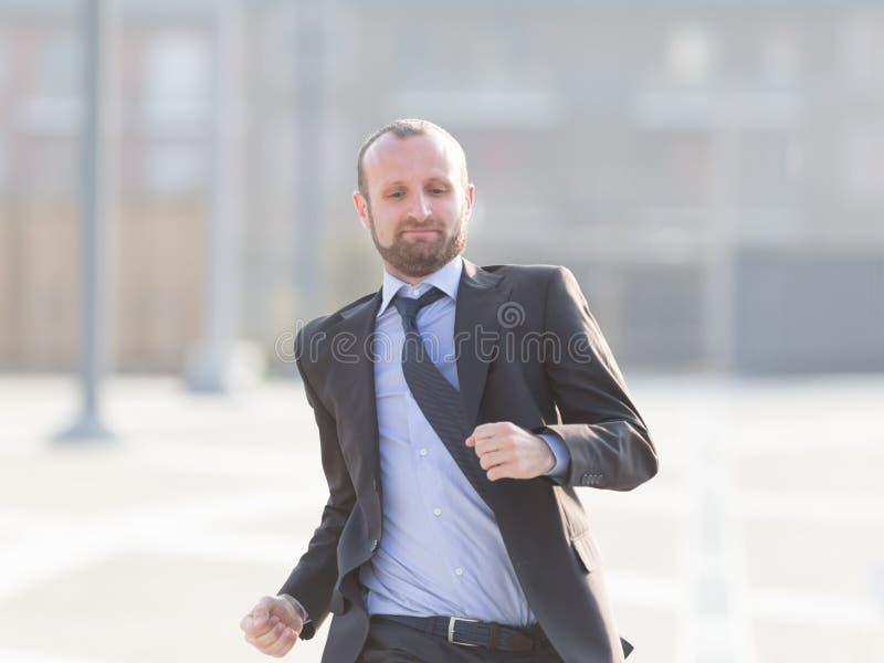 Homme d'affaires heureux courant dans la ville image stock