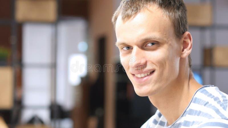 Homme d'affaires heureux de mi-adulte s'asseyant au bureau, portrait riant photos stock