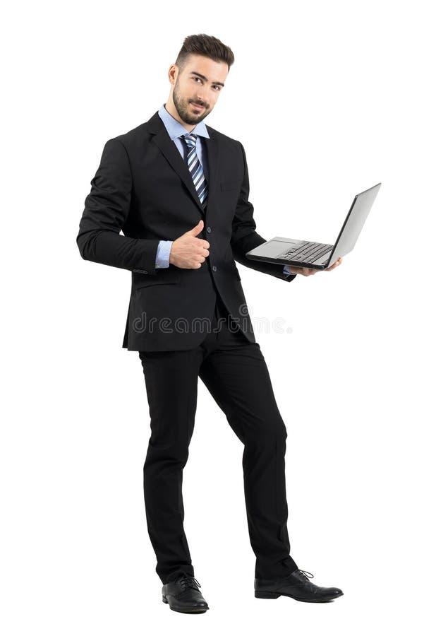 Homme d'affaires heureux de sourire avec l'ordinateur portable montrant le pouce vers le haut du geste regardant l'appareil-photo photographie stock libre de droits