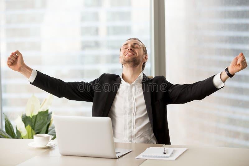 Homme d'affaires heureux de sourire célébrant le projet de travail de finition à photographie stock