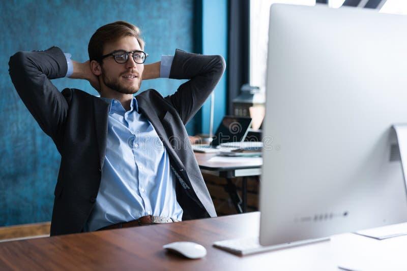 Homme d'affaires heureux de sourire dans les verres et la chemise bleue détendant dans le bureau après jour ouvrable dur image libre de droits