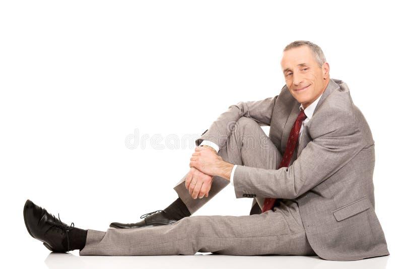 Homme d'affaires heureux de vue de côté s'asseyant sur le plancher image stock