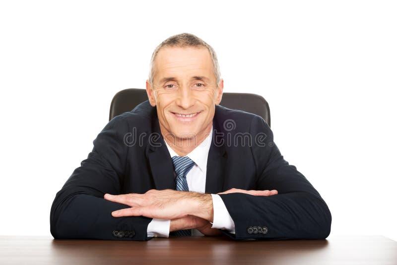 Homme d'affaires heureux s'asseyant à son bureau photos stock
