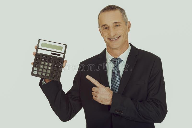 Homme d'affaires heureux se dirigeant sur la calculatrice image libre de droits