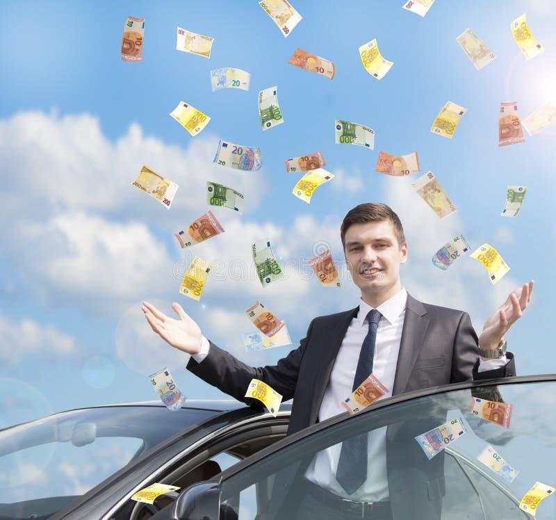 Homme d'affaires heureux se tenant sous la pluie de l'argent images libres de droits
