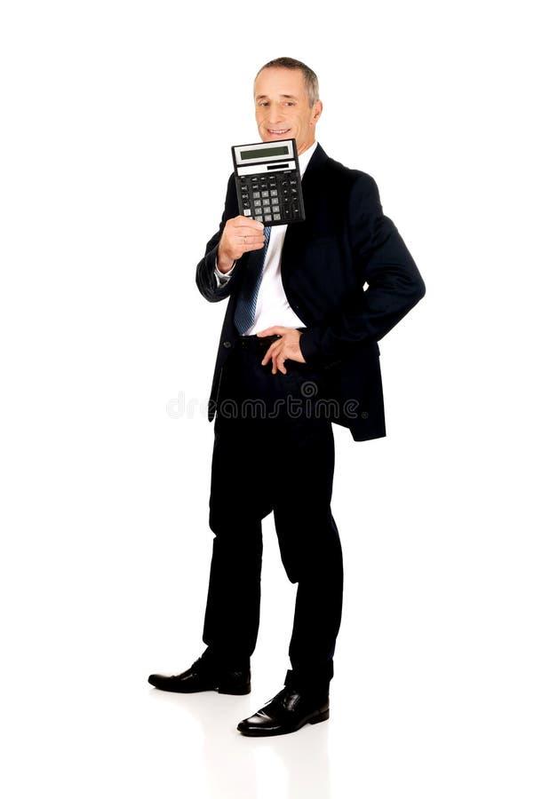 Homme d'affaires heureux tenant une calculatrice images stock