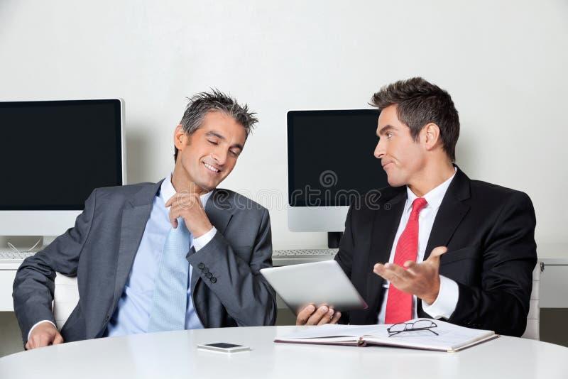 Homme d'affaires Holding Digital Tablet s'asseyant avec image libre de droits