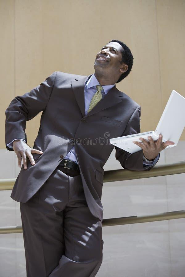 Homme d'affaires Holding Laptop And recherchant photographie stock