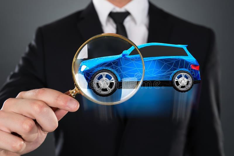 Homme d'affaires Holding Magnifying Glass en Front Of Blue Car photos stock