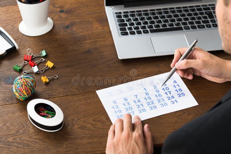 Homme d'affaires Holding Pen Over Calendar images libres de droits