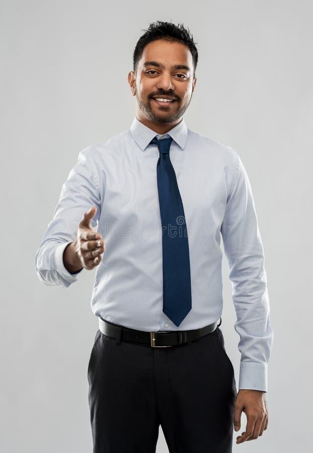 Homme d'affaires indien étirant la main pour la poignée de main images stock