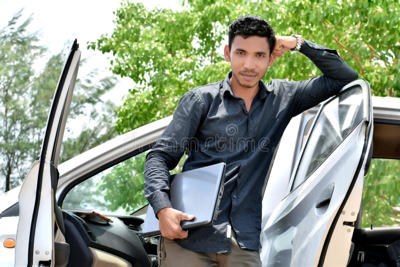 Homme d'affaires indien bel travaillant sur l'ordinateur portable avec la voiture photo libre de droits