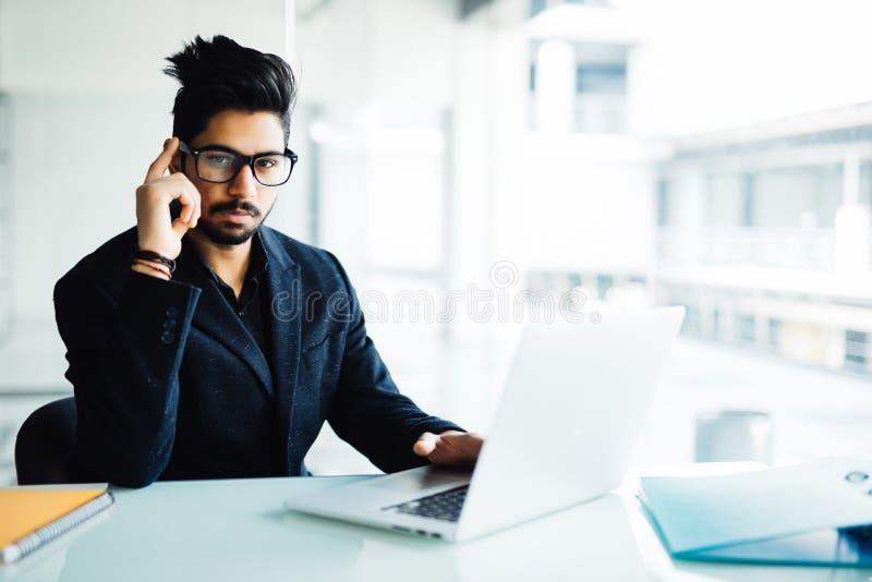 Homme d'affaires indien confus travaillant sur l'ordinateur portable dans le bureau Jeune homme indien pensant au-dessus du proje photographie stock libre de droits