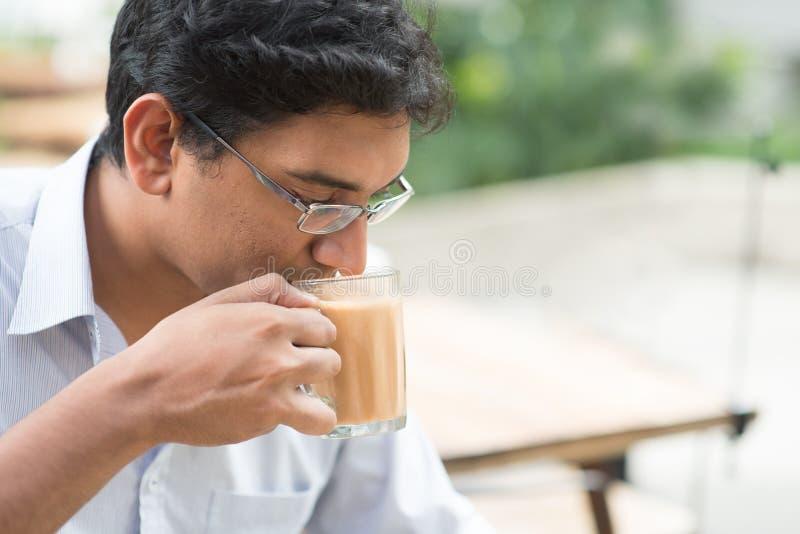 Homme d'affaires indien sirotant un thé chaud de lait de tasse image stock