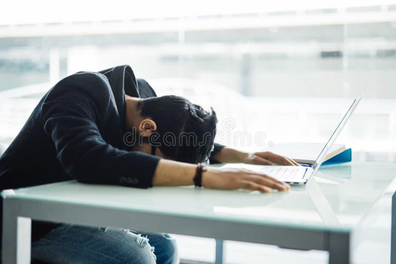 Homme d'affaires indien Sleeping au-dessus de l'ordinateur portable dans le bureau moderne photographie stock