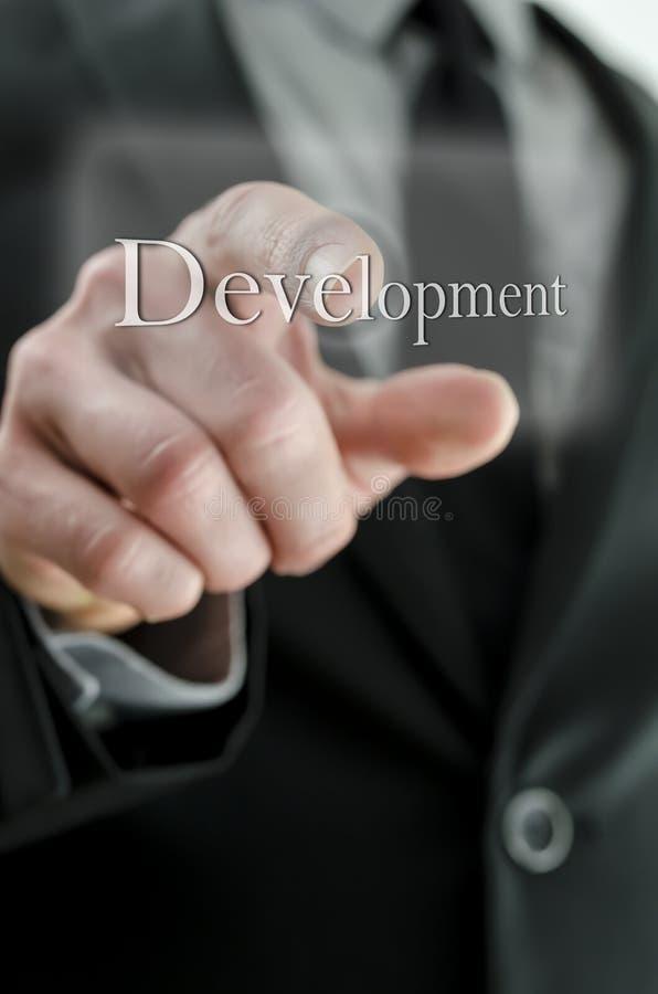 Homme d'affaires indiquant l'icône de développement sur un écran virtuel images stock