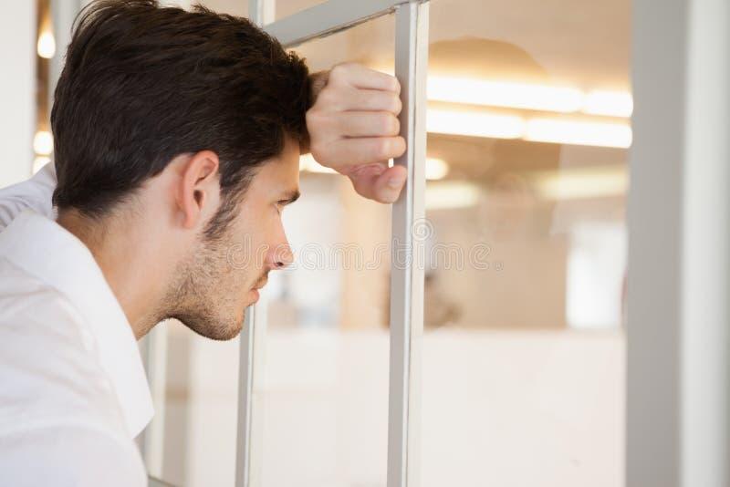 Homme d'affaires inquiété occasionnel se penchant contre la fenêtre image stock