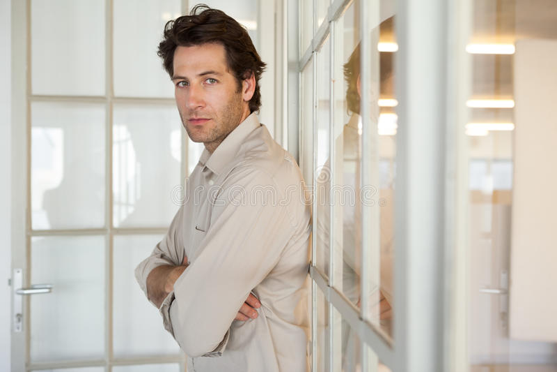 Homme d'affaires inquiété occasionnel se penchant sur la fenêtre photo stock