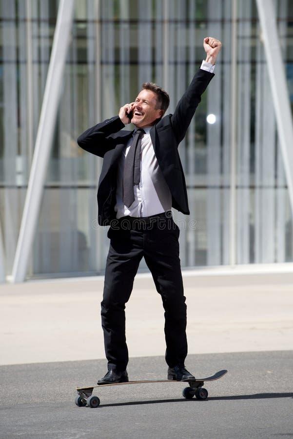 Homme d'affaires intégral d'amusement se tenant sur la planche à roulettes sur l'appel téléphonique photos libres de droits