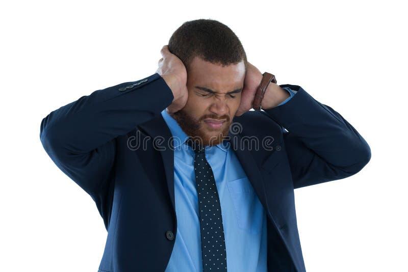 Homme d'affaires irrité couvrant ses oreilles photographie stock libre de droits