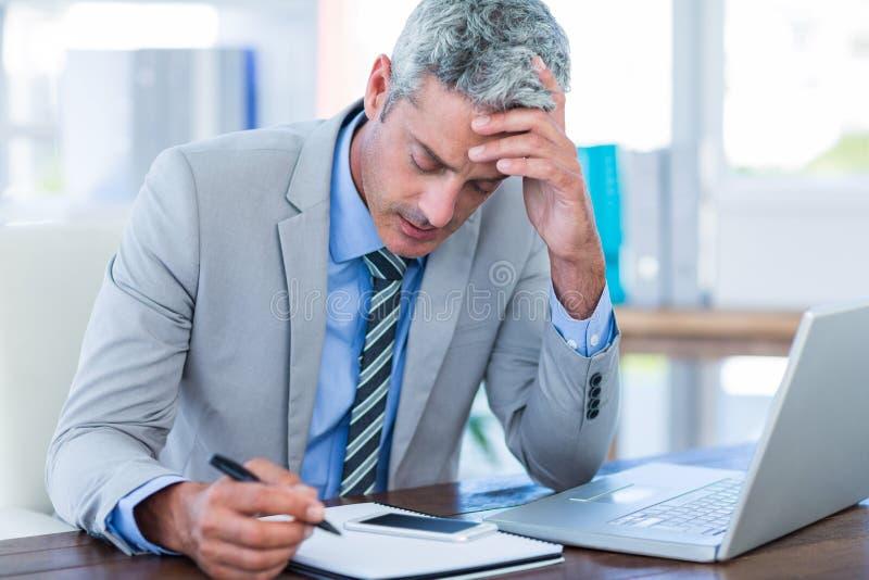 Homme d'affaires irrité essayant de travailler photos stock