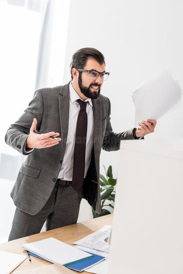homme d'affaires irrité tenant des documents et criant images libres de droits