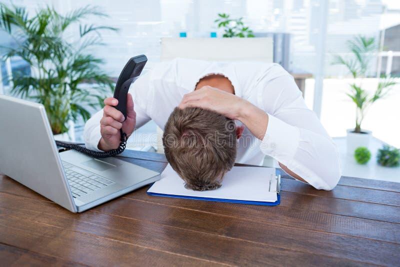 Homme d'affaires irrité tenant une ligne téléphone de terre image stock
